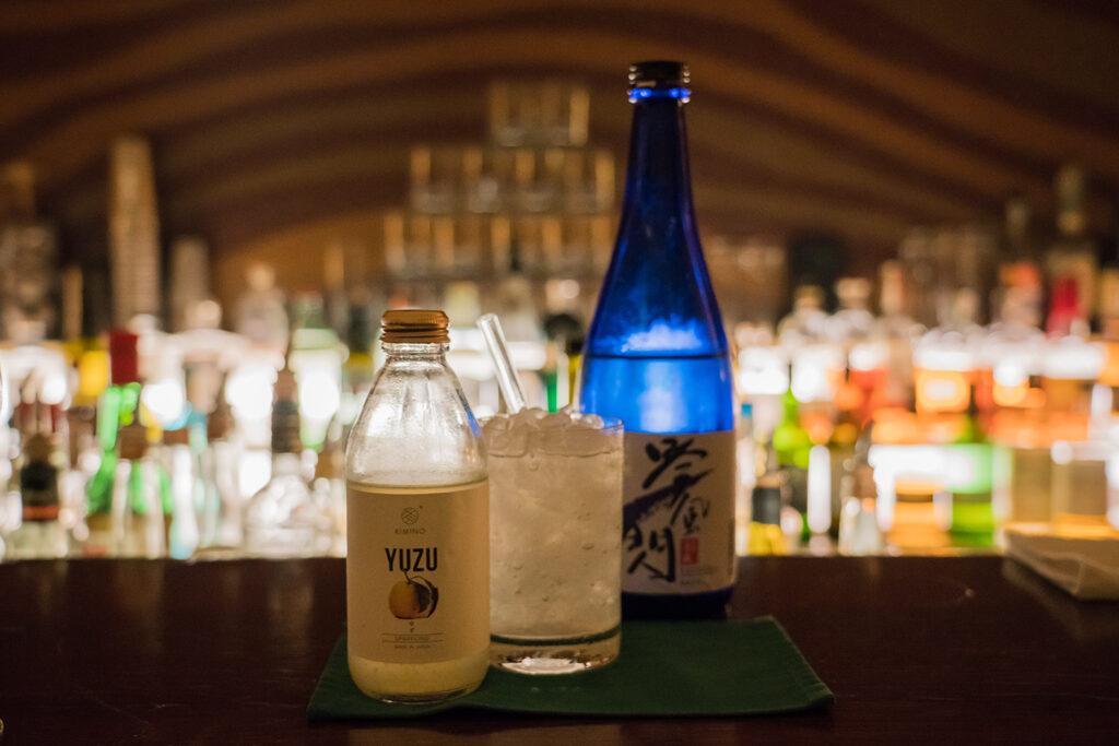 East Meets West -  Ein erfrischender Cocktail der japanischen Sake mit mexikanischem Mezcal kombiniert. Abgerundet mit einem Dash Ananas und aufgefüllt mit einem spritzigen KIMINO Yuzu Sparkling